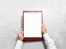 Рука держа пустую красную доску сзажимом для бумаги с модель-макетом дизайна белой бумаги Стоковое Изображение