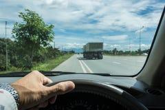 Рука держа рулевое колесо около дороги для безопасного привода Стоковые Изображения