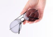 Рука держа серые солнечные очки Стоковая Фотография