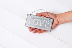 Рука держа слово влюбленности на белизне Стоковая Фотография