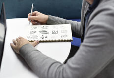 Рука держа тетрадь с нарисовала идеи дизайна логотипа бренда творческие Стоковое Изображение
