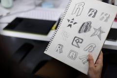 Рука держа тетрадь с нарисовала идеи дизайна логотипа бренда творческие Стоковое фото RF