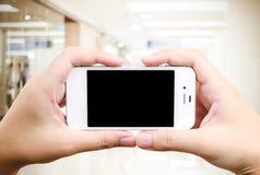 Рука держа умный телефон над предпосылкой магазина нерезкости Стоковое фото RF