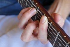 Рука держа хорду гитары Стоковое Фото