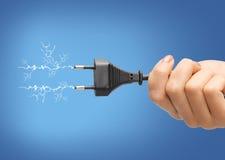 Рука держа черную электрическую штепсельную вилку с проводом стоковая фотография