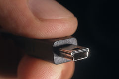 Рука держа черный мини кабель USB Рука человека держит соединитель USB мини Стоковые Изображения