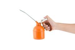 Рука держа чонсервную банку оранжевого масла стоковая фотография