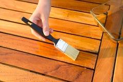 Рука держа щетку прикладывая краску политуры на деревянной таблице сада стоковые фотографии rf