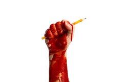 Рука держа pensil в крови как символ shooti Чарли Hebdo Стоковое Изображение