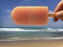 Рука держа popsicle горизонтально над морем Стоковое фото RF