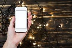 Рука держа smartphone на деревянной предпосылке Стоковые Фотографии RF