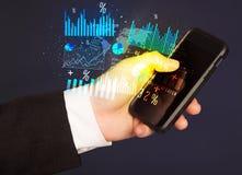 Рука держа smartphone с диаграммами дела Стоковые Фото