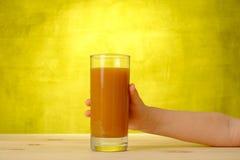 Рука детей держит сок персика в стекле Стоковые Изображения RF