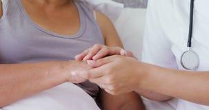 Рука женского доктора рассматривая старшей женщины 4k видеоматериал