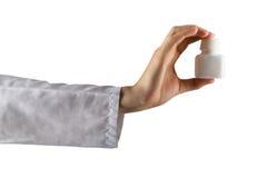 Рука женского доктора держа медицинские пилюльки изолированный на белой предпосылке помогите сперва Стоковое фото RF