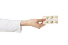 Рука женского доктора держа медицинские пилюльки изолированный на белой предпосылке помогите сперва Стоковое Изображение
