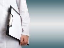 Рука женского доктора держа медицинскую доску сзажимом для бумаги с чистым листом Стоковое фото RF