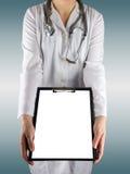 Рука женского доктора держа медицинскую доску сзажимом для бумаги с чистым листом бумаги и стетоскопа на сини запачкала предпосыл Стоковые Фотографии RF