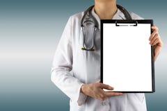 Рука женского доктора держа пустые медицинские доску сзажимом для бумаги и stethos Стоковые Изображения