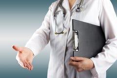 Рука женского доктора держа стетоскоп и доску сзажимом для бумаги на сини запачкала предпосылку Концепция здравоохранения и медиц Стоковое Изображение RF