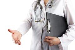 Рука женского доктора держа стетоскоп и доску сзажимом для бумаги на белой предпосылке Концепция здравоохранения и медицины Стоковые Изображения