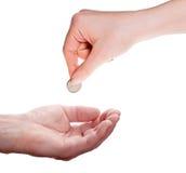 Рука женщины давая монетку к руке человека Стоковое фото RF