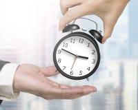 Рука женщины давая один будильник к руке человека Стоковые Изображения