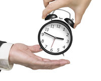 Рука женщины давая один будильник к руке человека Стоковая Фотография