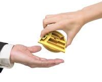 Рука женщины давая шестерню символа валюты к руке человека Стоковые Фотографии RF