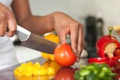 Рука женщины афроамериканца отрезая tomatoe Стоковые Фотографии RF