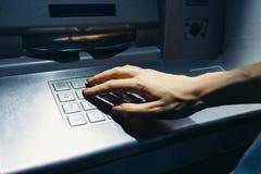 Рука женщины входит в секретный код на ATM на улице на Стоковые Изображения