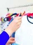 Рука женщины выбирая платье Стоковое Фото