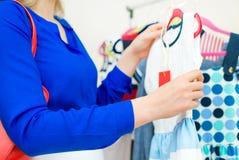 Рука женщины выбирая платье Стоковая Фотография