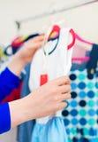 Рука женщины выбирая платье Стоковые Изображения