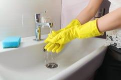 Рука женщины в желтой резиновой перчатке в потоке воды стоковое изображение rf