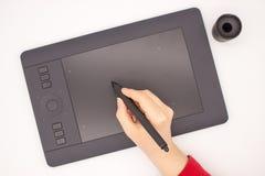Рука женщины в красном рукаве рисует грифель на планшете графиков стоковые фотографии rf
