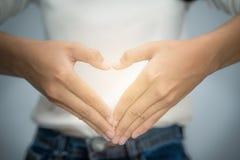 Рука женщины делая форму сердца с ее пальцами Стоковая Фотография RF