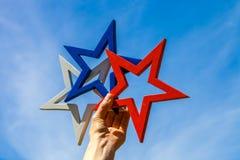 Рука женщины держа белую, голубую и красную звезду против голубого неба Стоковая Фотография