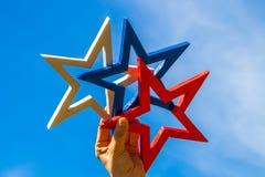 Рука женщины держа белую, голубую и красную звезду против голубого неба Стоковые Изображения