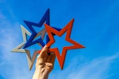 Рука женщины держа белую, голубую и красную звезду против голубого неба Стоковое Фото