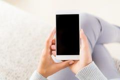 Рука женщины держа белый мобильный телефон и сидя на софе Стоковая Фотография RF