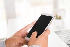 Рука женщины держа белый мобильный телефон на таблице с компьтер-книжкой i стоковое фото