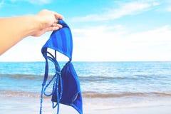Рука женщины держа бикини с морем и голубое небо в предпосылке, счастливой Стоковые Изображения