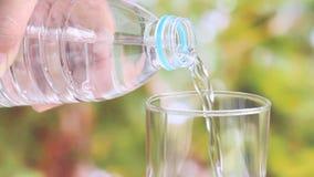 Рука женщины держа бутылку с водой и лить ясной питьевой воды в стекло на запачканной зеленой предпосылке природы сток-видео