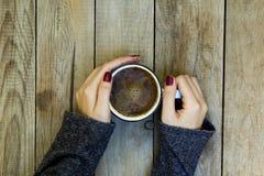 Рука женщины держа кофейную чашку на деревянном столе стоковая фотография rf