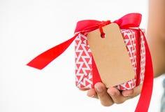 Рука женщины держа красную подарочную коробку с космосом экземпляра карточки бирок стоковые фотографии rf