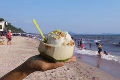 Рука женщины держа мороженое в свежей чашке кокоса брызгает с арахисами на пляже в лете Стоковые Изображения