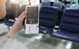 Рука женщины держа пасспорт и билет полета в авиапорте стоковое фото