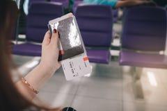 Рука женщины держа пасспорт и билет полета в авиапорте стоковая фотография