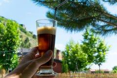 Рука женщины держа стекло холодного кофе outdoors, освежая время кофе Стоковые Изображения
